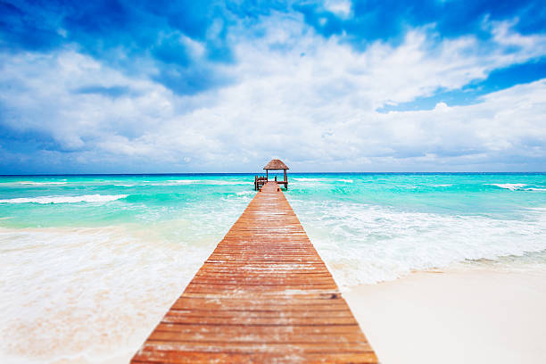 tropical beach with jetty. mexico. riviera maya. - playa del carmen stock photos and pictures