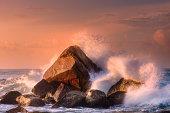 Tropical beach with rocks and big crashing waves at sunset Mirissa, Sri Lanka