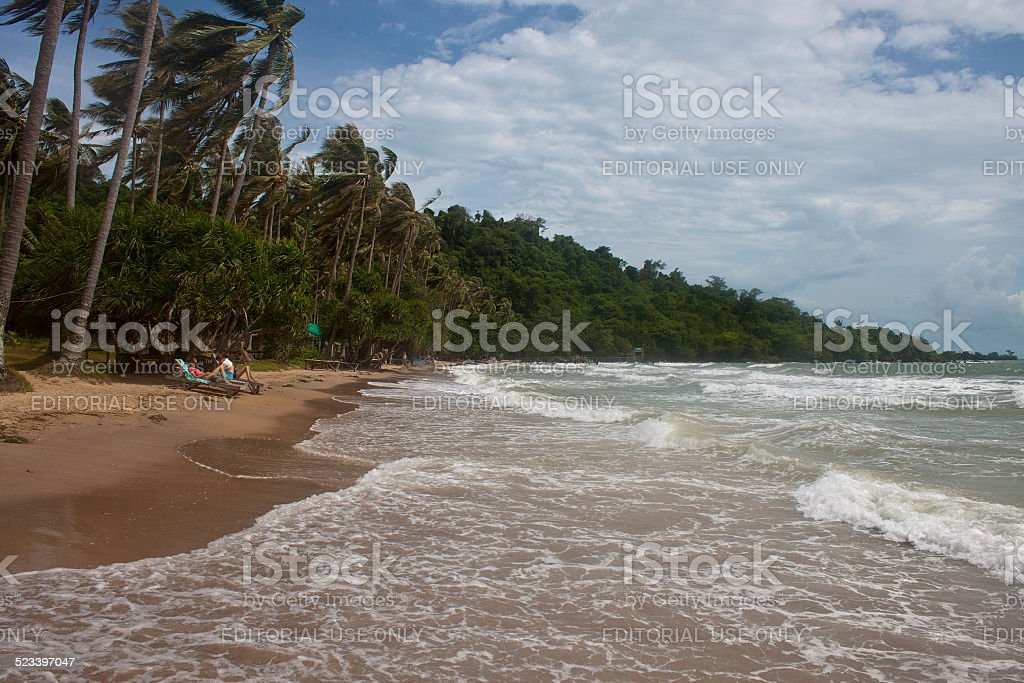 Tropical beach with tourists stock photo