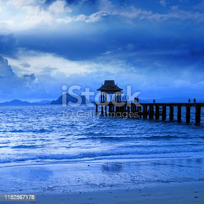Beautiful tropical beach with wooden pier and blue sea water over cloudy sky in morning time in Phuket island, Thailand