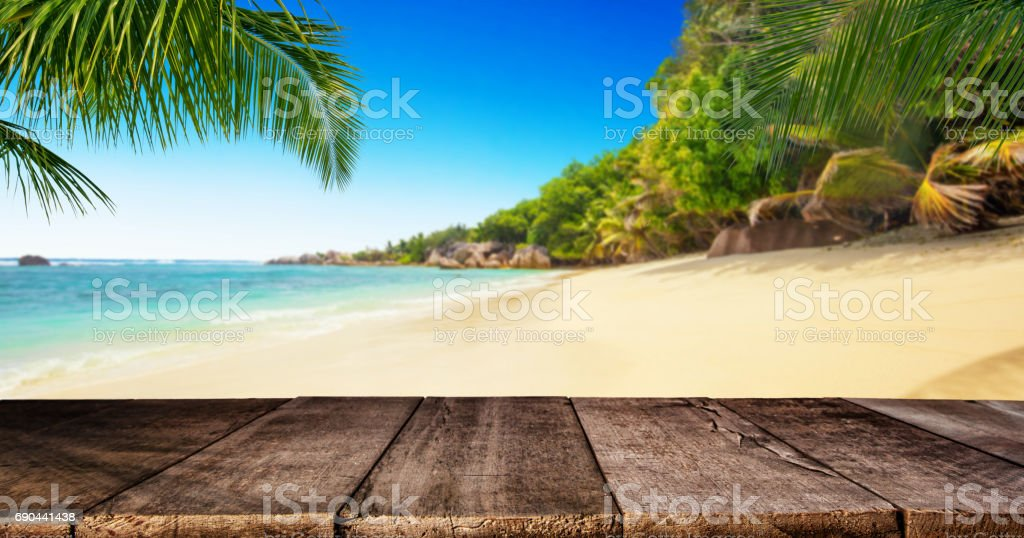 Tropical beach with wooden table, summer holiday background. stock photo