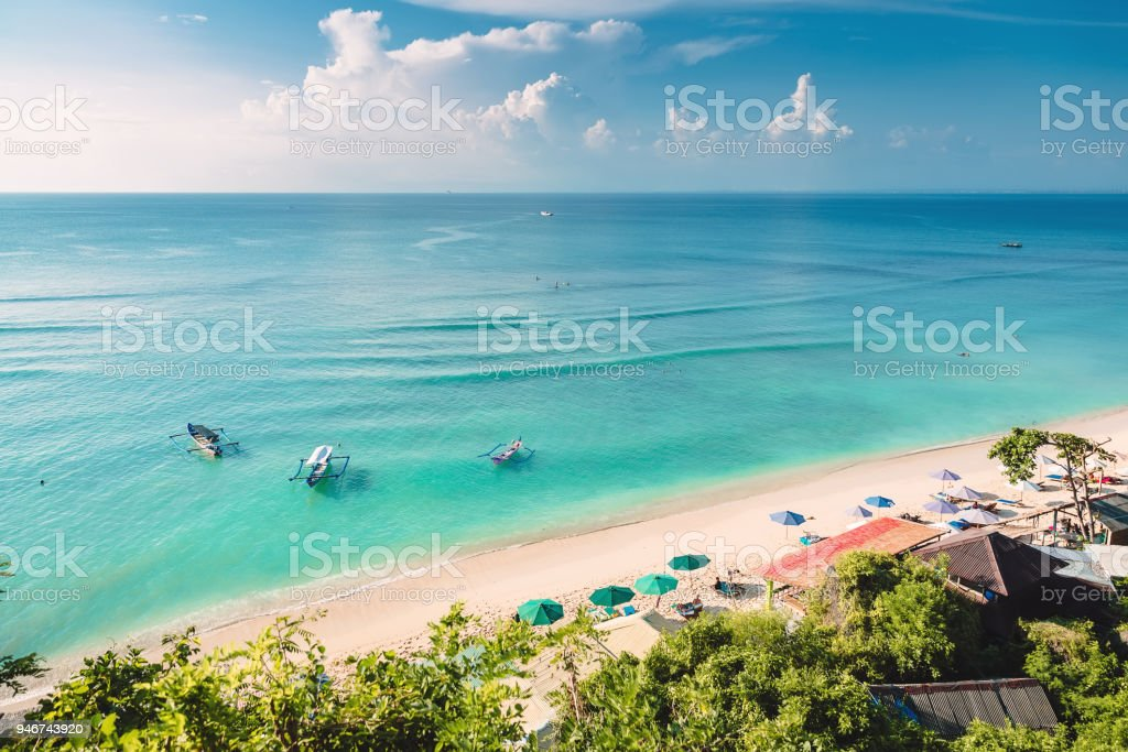 Tropical blue ocean, sandy beach and boats in Indonesia, Bali stock photo
