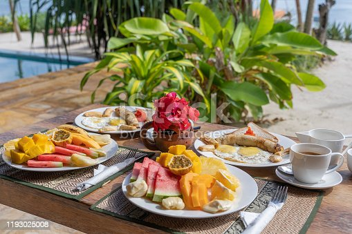 Tropical breakfast of fruit, coffee and scrambled eggs and banana pancake for two on the beach near sea in hotel restaurant, island Zanzibar, Tanzania, Africa, close up
