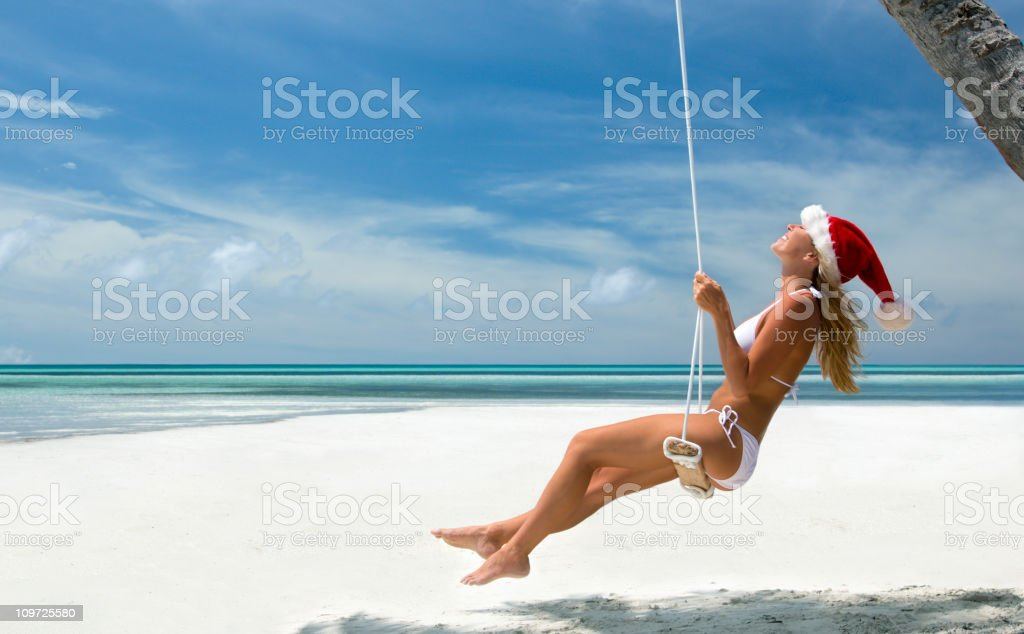Tropical Christmas woman on a swing stock photo