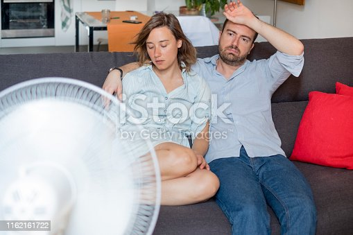 Stressed couple trying to refresh from summer heatwave