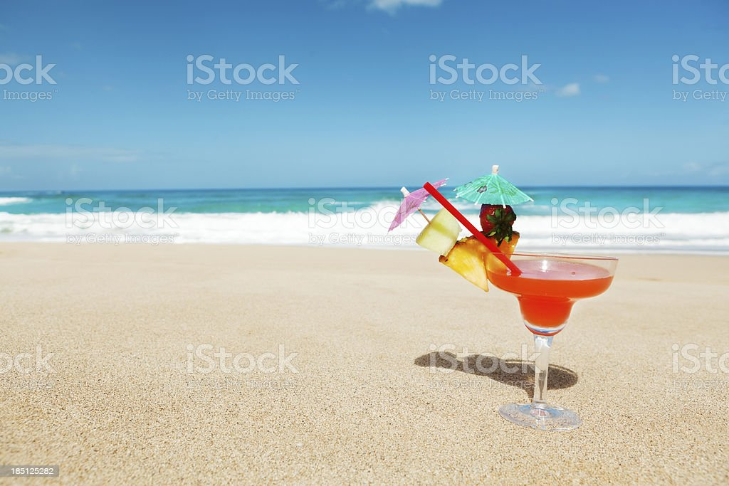 Tropical Cocktail Drink with Umbrella on a Sandy Beach Hz royalty-free stock photo