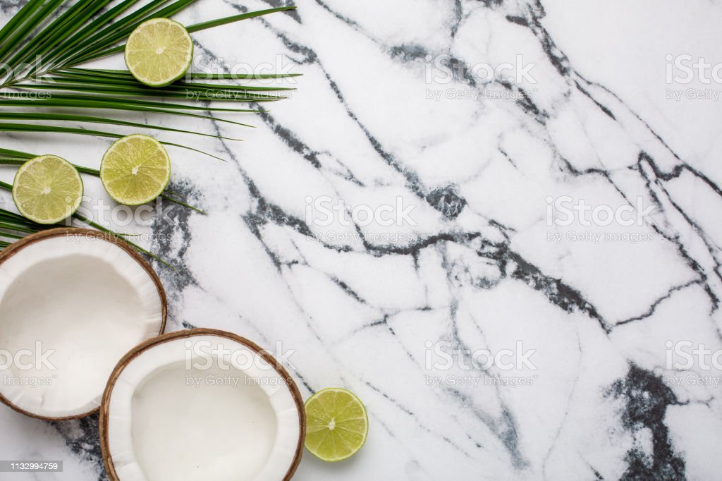 Tropical coconut, palm and lime on marble background stock photo
