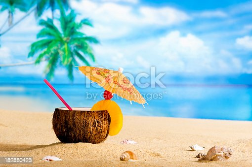 Tropical Coconut drink sitting in the sand on the beach with palm trees and ocean in the background
