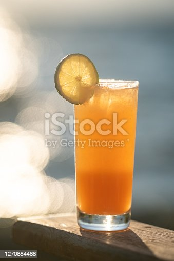 A close up of a perfectly refreshing Mai Tai resting outside on a chair by the side of a lake. The gradient blues of the lake and the sky above the horizon are soft and out of focus in the background. The Sun is setting on a cloudless day and the sunlight reflects off the water. The drink is garnished with a lime wheel.