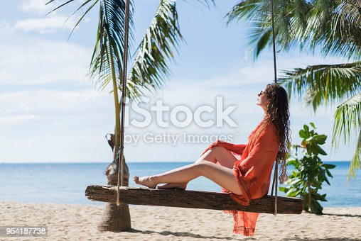 Beautiful caucasian woman sunbathing on a rope swing and enjoying a carefree summer day at the beach.