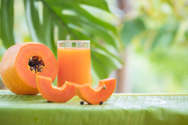 Tropical exotic papaya fruit and glass jar with smoothie shake j Tropical exotic papaya fruit and glass jar with smoothie shake juice drink outdoors with palm leaves papaya smoothie stock pictures, royalty-free photos & images