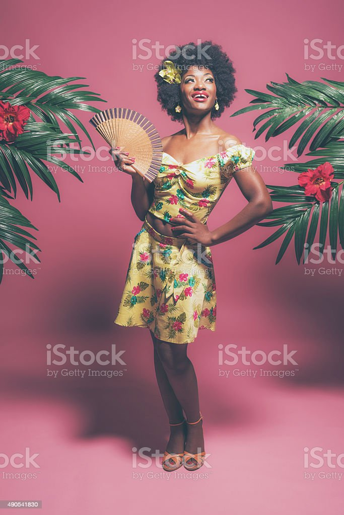 Tropical Fashion Afro American Pin-up Holding Fan. Against Pink. stock photo
