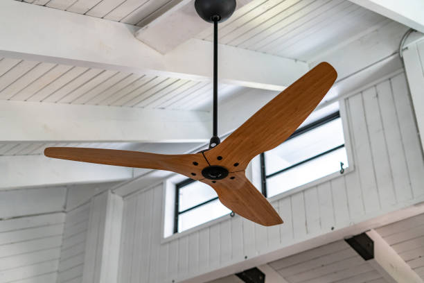 Tropical Florida Keys house interior fan and celing Traditionally built Florida Keys with white wooden walls and ceiling  with upper crank out vent windows with bamboo finish large ceiling fan. Could be used for multiple purposed including interior design, tropical style, beamed ceiling, and clerestory windows. ceiling fan stock pictures, royalty-free photos & images