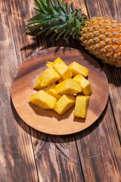 tropische früchte-konzept. geschnittenen ananas auf den alten hölzernen hintergrund. - ananas marmelade stock-fotos und bilder