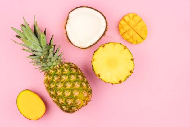 tropikal meyve düz pastel pembe bir arka plan üzerinde yatıyordu. köşe yönlendirme. - hindistan cevizi tropik meyve stok fotoğraflar ve resimler