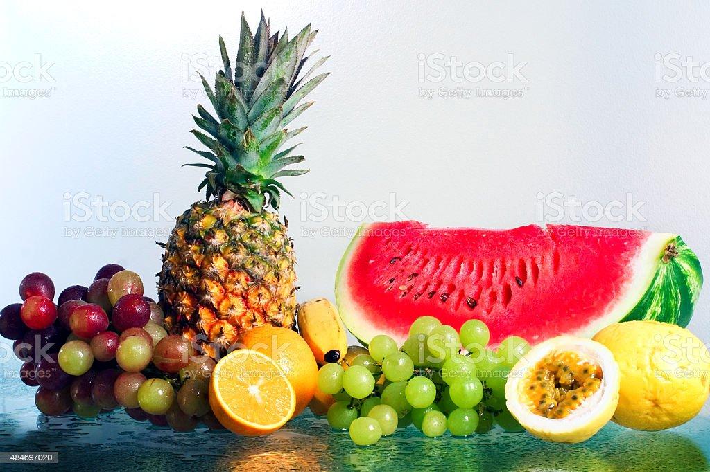 Frutas tropicais de laranja, abacaxi, melancia, uvas Bananas na superfície molhada - foto de acervo