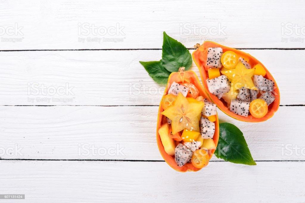 Tropical Fruit Salad Served in half a Papaya. Dragon Fruit, rambutan, tamarind, cactus fruit, avocado, mango. On a wooden background. Top view. stock photo