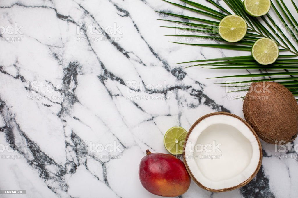 Tropical fruits and coconut on marble background stock photo