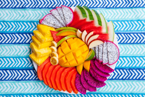 Tropical fruits assortment on a white plate, blue colorful textile background. Top view. Copy space. Tropical fruits assortment on a white plate, blue colorful textile background. Top view. Copy space papaya smoothie stock pictures, royalty-free photos & images