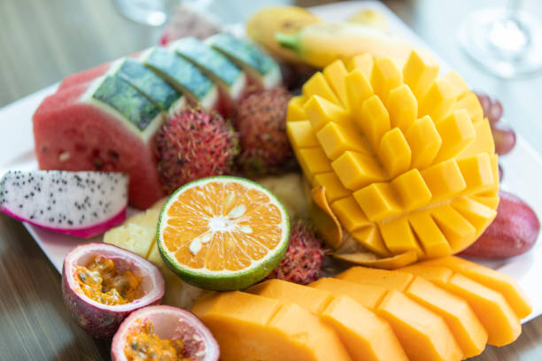 Tropical fruits assortment on a white plate served with wine in hotel room Tropical fruits assortment on a white plate served with wine in hotel room papaya smoothie stock pictures, royalty-free photos & images
