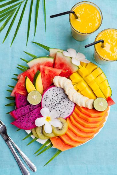 tropiska frukter sortimentet på en vit platta med palm tree löv med mango smoothie, textil blå bakgrund. ovanifrån. kopiera utrymme - cactus lime bildbanksfoton och bilder
