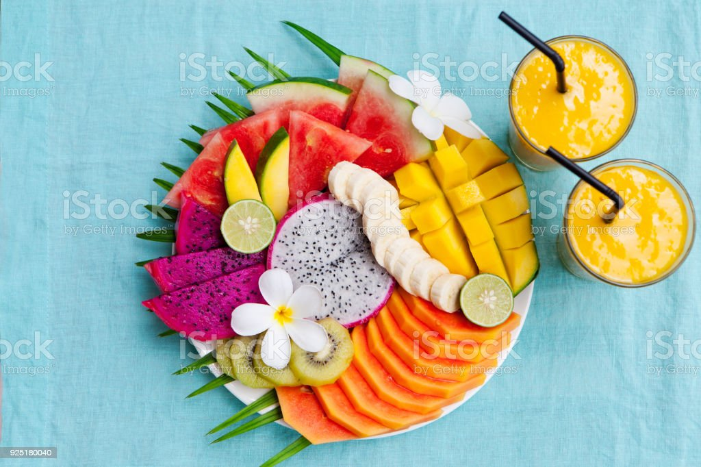 Tropical fruits assortment on a white plate with palm tree leaf with mango smoothie, textile blue background. Top view. Copy space stock photo