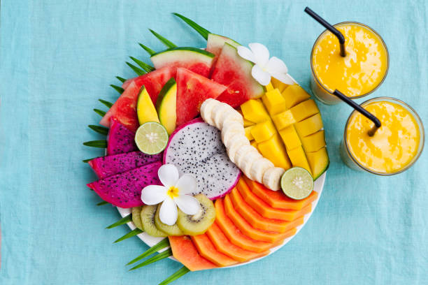 Tropical fruits assortment on a white plate with palm tree leaf with mango smoothie, textile blue background. Top view. Copy space Tropical fruits assortment on a white plate with palm tree leaf with mango smoothie, textile blue background. Top view. Copy space fruit salad stock pictures, royalty-free photos & images