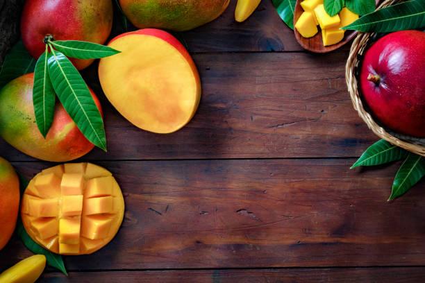 Fruits tropicaux : panier avec des mangues faisant un cadre avec l'espace de copie dans la cuisine rustique - Photo