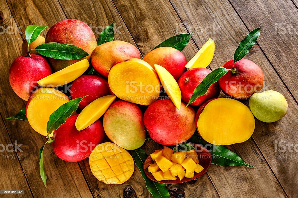 Tropical fruits group of ripe mangoes on wooden rustic table stock photo