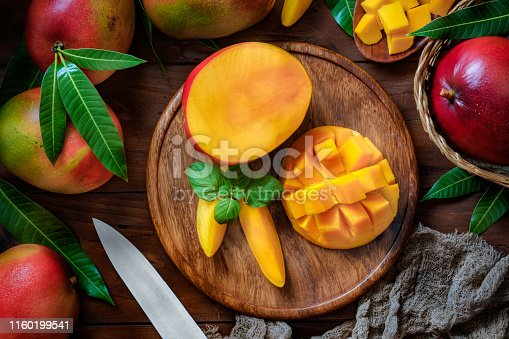 Healthy eating themes. Tropical Fruits: Sliced mangos in a wooden plate on a table in rustic kitchen