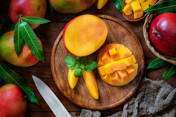 Tropical Fruits: Sliced mangos in a wooden plate on a table in rustic kitchen Healthy eating themes. Tropical Fruits: Sliced mangos in a wooden plate on a table in rustic kitchen mango stock pictures, royalty-free photos & images