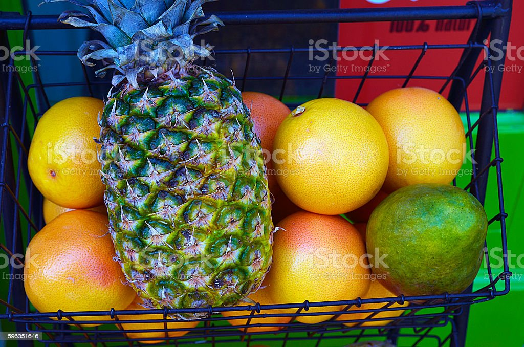 Tropical fruits:pineapple,oranges and mango in a basket outdoor. Lizenzfreies stock-foto