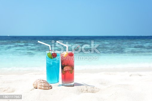Tropical fruity cocktails on white sandy beach
