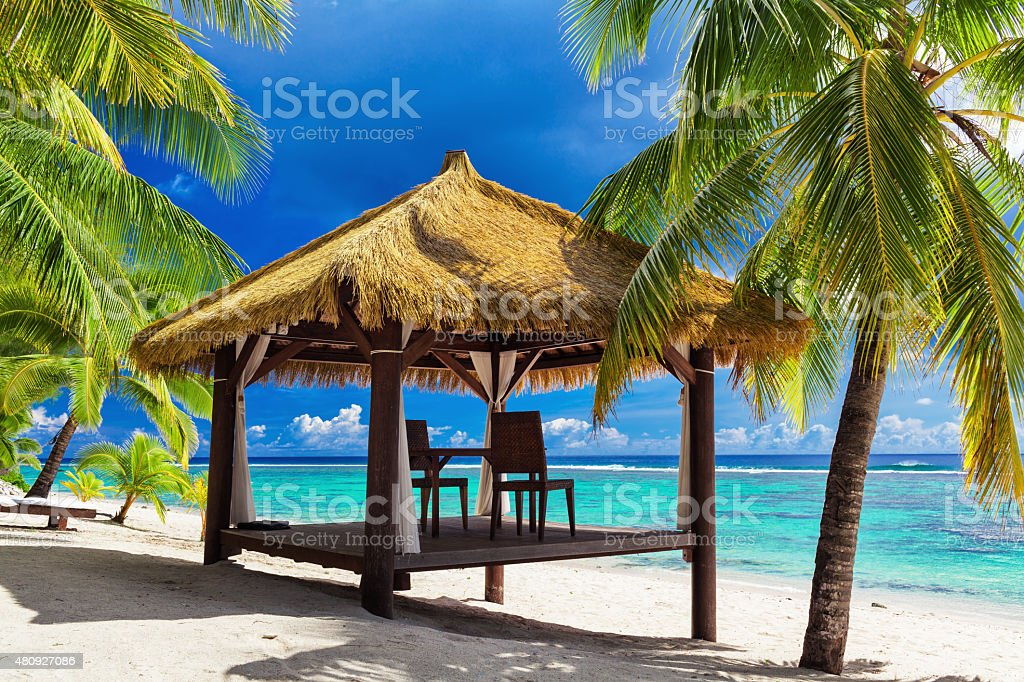 Tropical gazebo and two chairs on an island beach stock photo