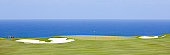 A beautiful golf course by the ocean. White sand bunkers. Kauai, Hawaii, United States. Golf scenic. Horizon over water. Horizontal colour image. Copyspace and blue sky. Panorama. This golf image shows the dramatic beauty of golfing in the tropical zone and, specifically, Hawaii. Kauai is one of the golfing hot spots in the state of Hawaii.