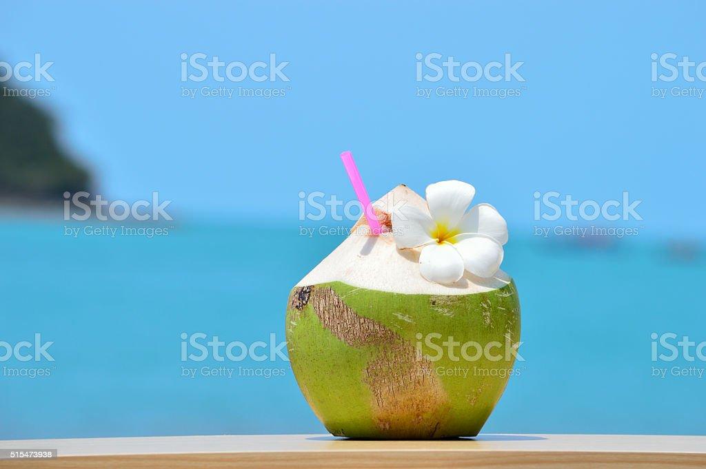 Coco Tropical verde com canudo na mesa de madeira contra - foto de acervo