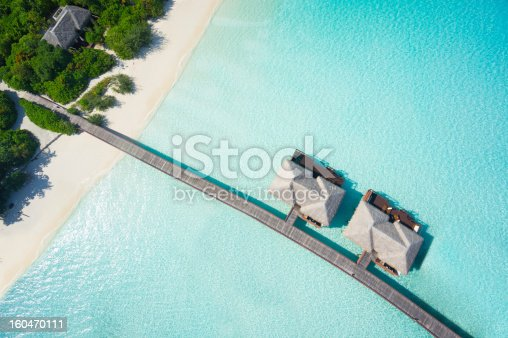 aerial top view island with jetty and overwater villas in tropical lagoon