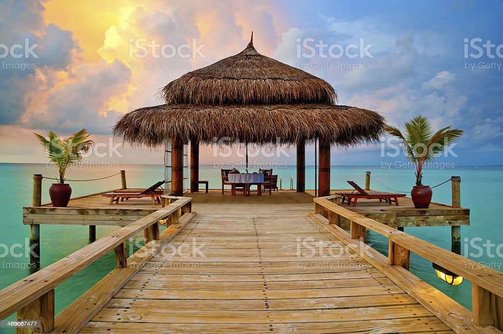 Tropical hut on water at sunset stock photo