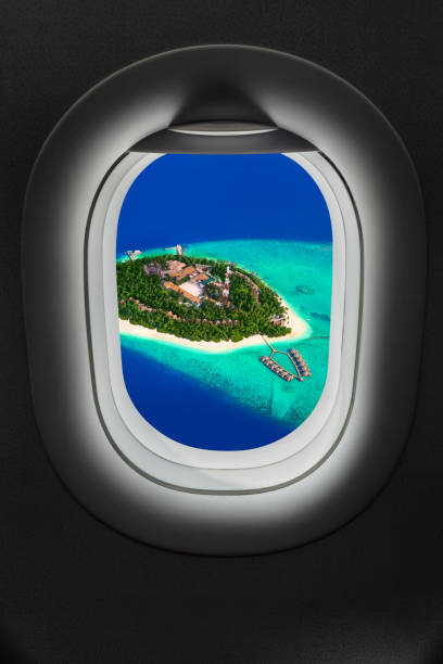 Tropical island at Maldives in airplane window stock photo