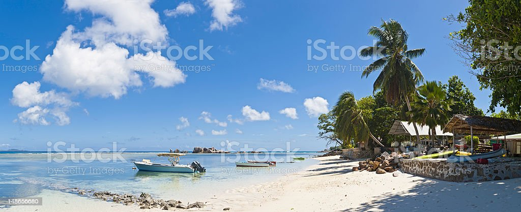 Tropical island beach house boats idyllic palm tree lagoon Seychelles Palm trees and white sands, fishing boats and beach huts in this picturesque tropical island panorama of clear turquoise lagoon under big blue Indian Ocean skies in the Seychelles, Africa. ProPhoto RGB profile for maximum color fidelity and gamut. Absence Stock Photo
