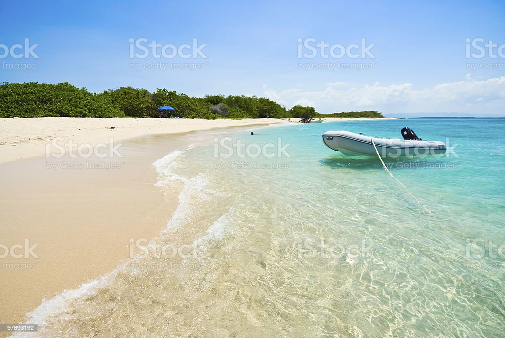 Tropical island beach with a boat royalty-free stock photo