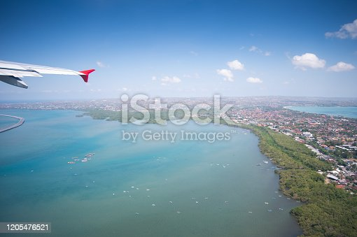 1058205304 istock photo Tropical island coastline view from the plane island sneak peaking through the clouds seen from a plane's window Bali ,Indonesia 1205476521