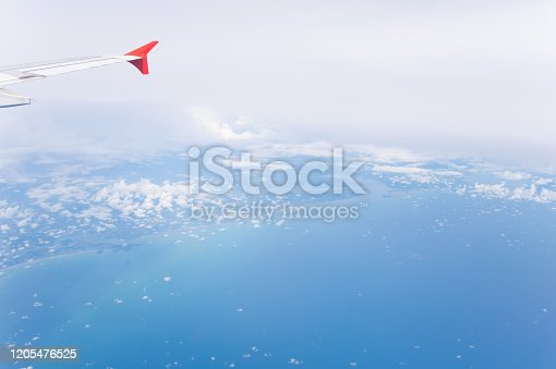 1058205304 istock photo Tropical island coastline view from the plane island sneak peaking through the clouds seen from a plane's window Bali ,Indonesia 1205476525