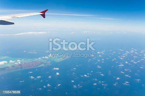 1058205304 istock photo Tropical island coastline view from the plane island sneak peaking through the clouds seen from a plane's window Bali ,Indonesia 1205476539