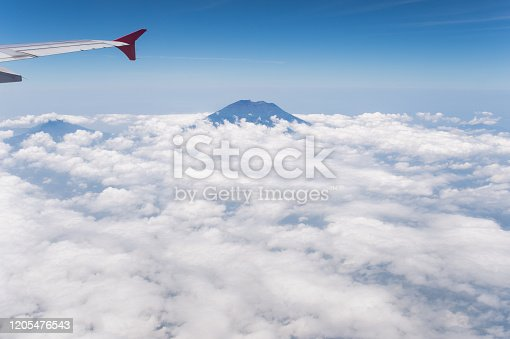 1058205304 istock photo Tropical island coastline view from the plane island sneak peaking through the clouds seen from a plane's window Bali ,Indonesia 1205476543