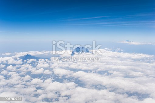1058205304 istock photo Tropical island coastline view from the plane island sneak peaking through the clouds seen from a plane's window Bali ,Indonesia 1206752794