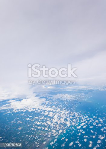 1058205304 istock photo Tropical island coastline view from the plane island sneak peaking through the clouds seen from a plane's window Bali ,Indonesia 1206752803