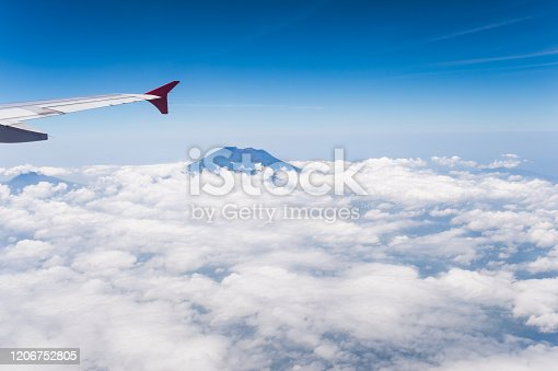 1058205304 istock photo Tropical island coastline view from the plane island sneak peaking through the clouds seen from a plane's window Bali ,Indonesia 1206752805