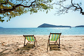 Tropical island scene with beach lounges on sand. Sunny day of tourists with swimming and deck chair near an ocean.