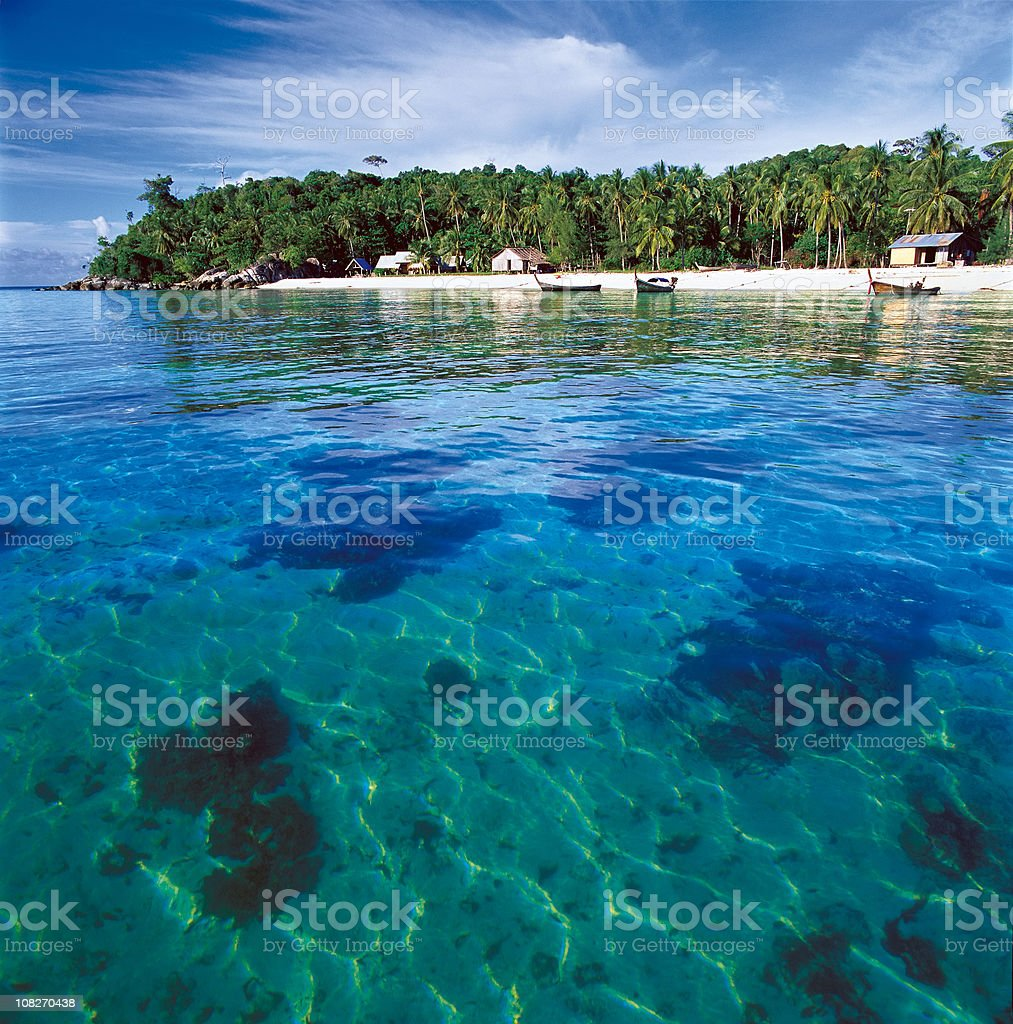 Tropical island with crystal ocean and palm fringed white beach. royalty-free stock photo